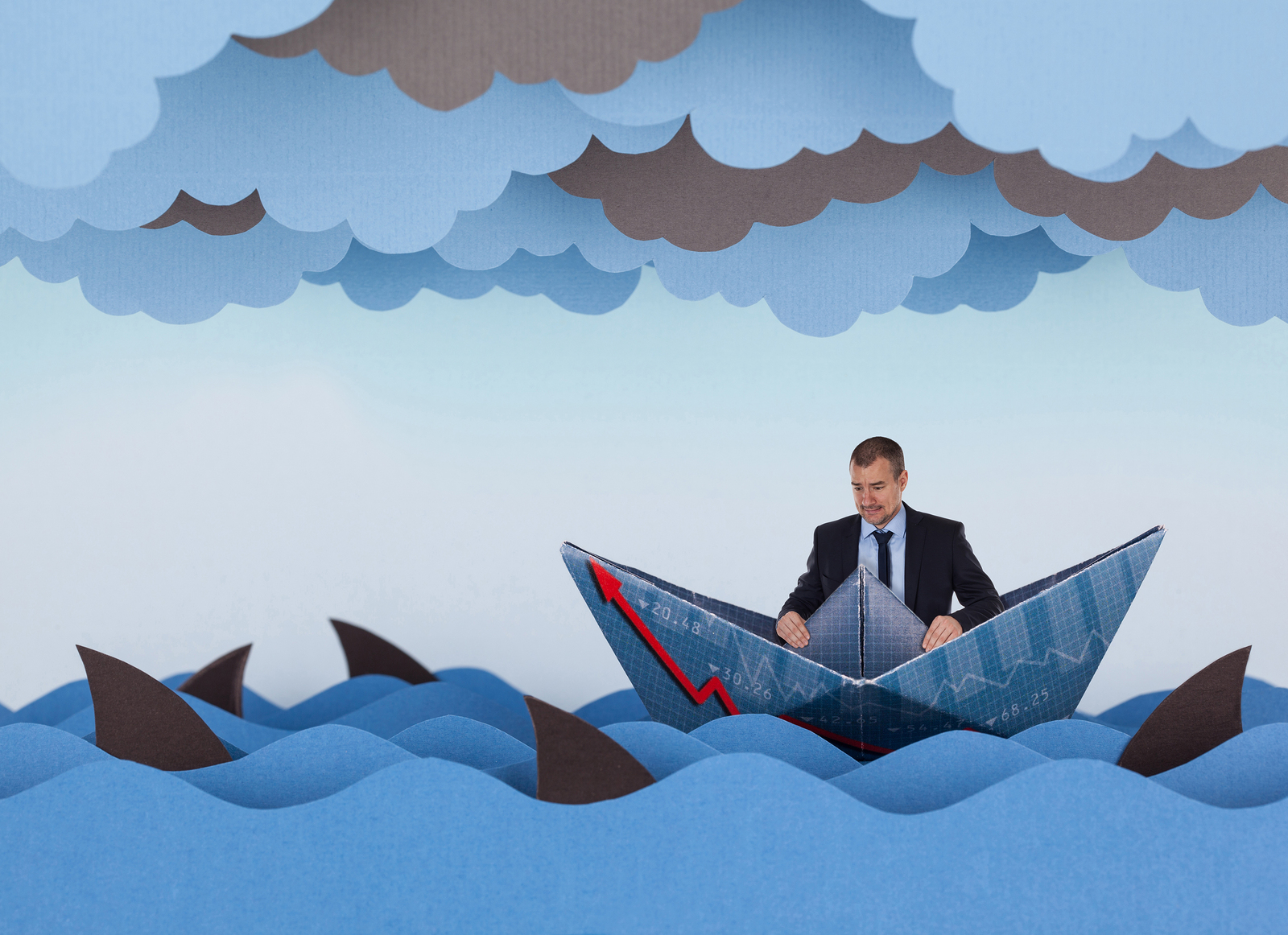 Businessman surrounded by sharks in stormy sea. Competitive business concept. Paper waves clouds boat and